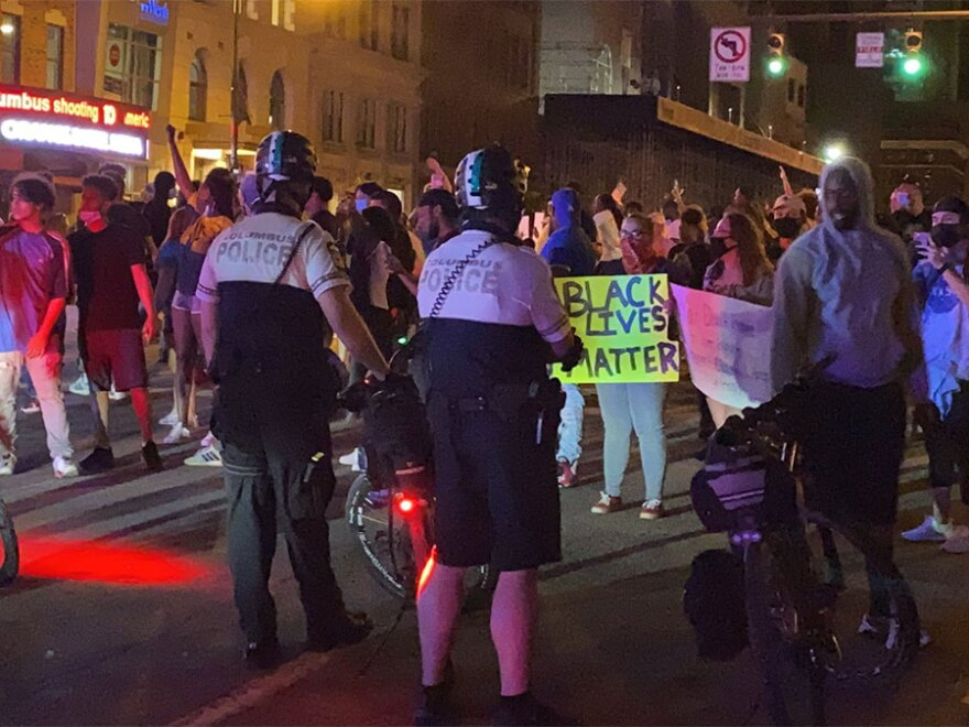 Police watch protestors in the streets at the intersection of Broad and High streets in downtown Columbus on Thursday.