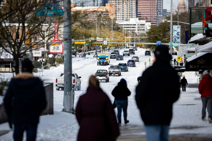 People and cars navigate their way through a snow and ice-covered South Congress Avenue on Monday.