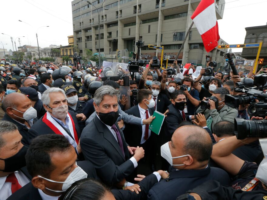 Francisco Sagasti, center with black mask, leaves the Congress in November after being chosen as the country's interim President. Sagasti was the third president in the span of a week. Political instability has hampered Peru's efforts to get vaccines.