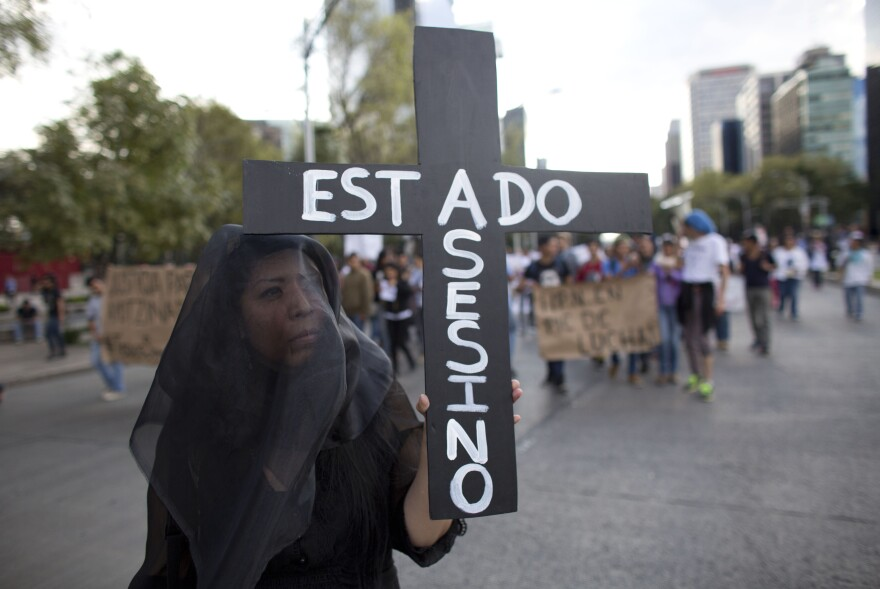 """A woman wears a black veil and carries a cross reading in Spanish """"Assassin State,"""" as thousands march down one of the capital's main boulevards to demand that the government find the 43 students who disappeared in southern Guerrero State."""