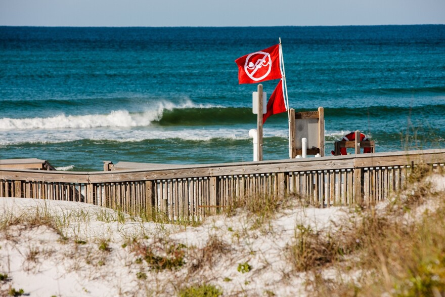 Beach with red flags flying