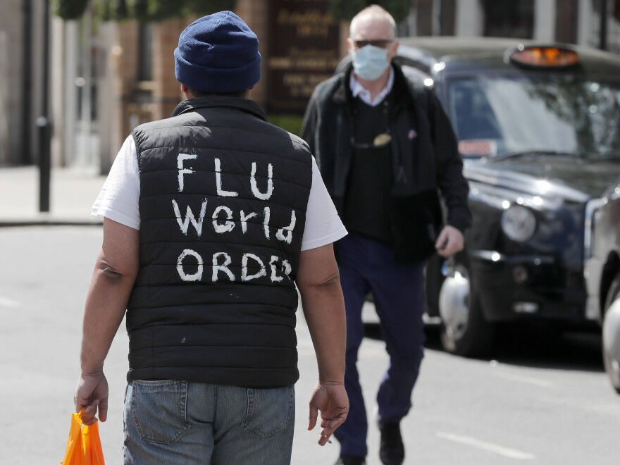 "A man with ""flu world order"" written on his back walks in London on Tuesday, as the U.K. continues its lockdown. The U.K. is doubling the length of its worker furlough program, citing the need to help employees when the economy reopens."