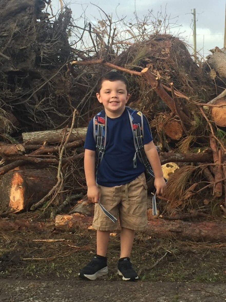 Tanner Livingston wears a backpack as he stands in front of pile of tree debris after Hurricane Michael. His Lynn Haven home was heavily damaged.