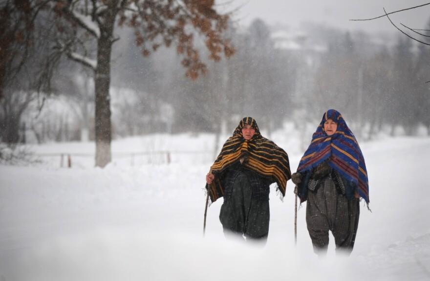 Bulgarian women walk during a snowfall in the village of Rakovski, northeast from capital Sofia.