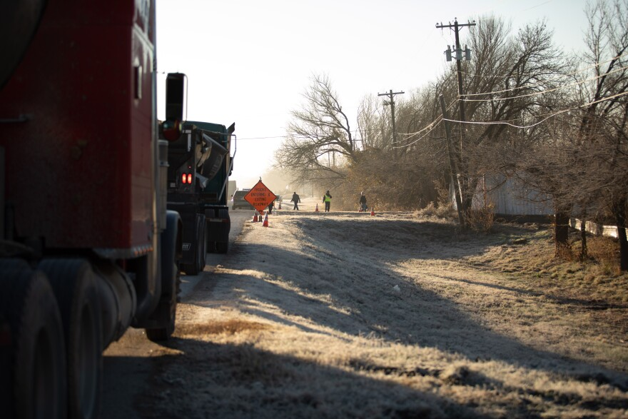 Trucks line up on the side of the road on Thursday morning. They're gearing up to remove the 100,000 ton pile of waste that has accumulated for the past three years.  Off at the distance there's a orange constructions sign and workers.