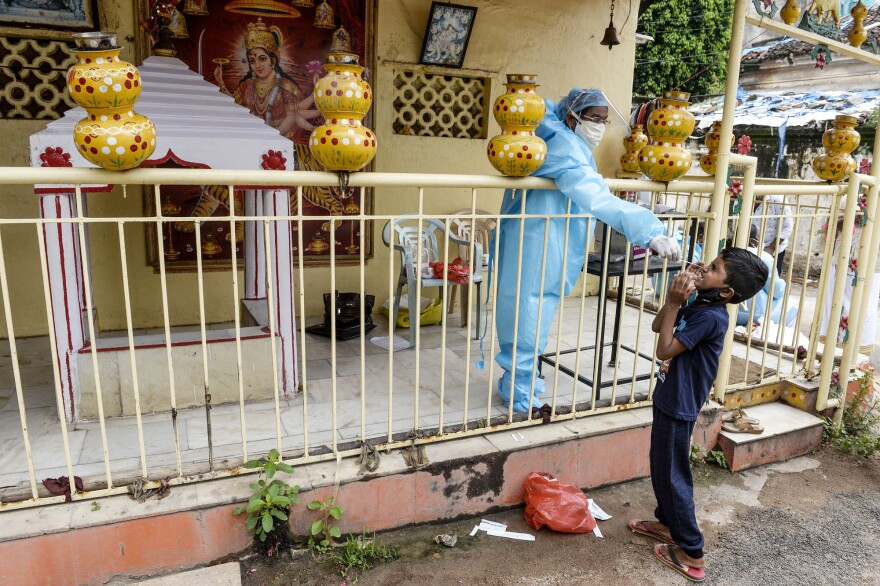 A health worker collects a swab sample from a boy for a coronavirus test at a temporary collection center at a Hindu temple in Hyderabad, the capital of the Indian state of Telangana, on Sept. 30, 2020.