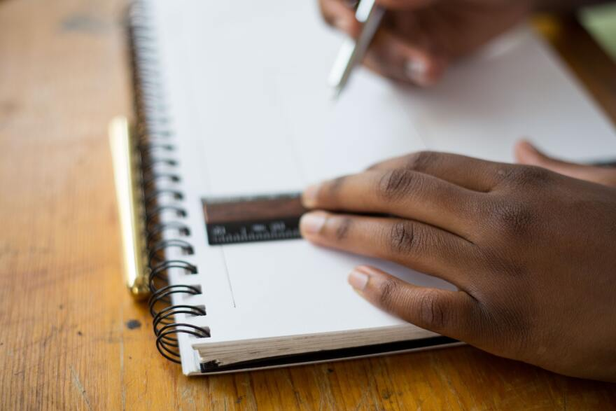 A Black child puts a ruler on their notebook and poises a pencil above the paper to start jotting things down.