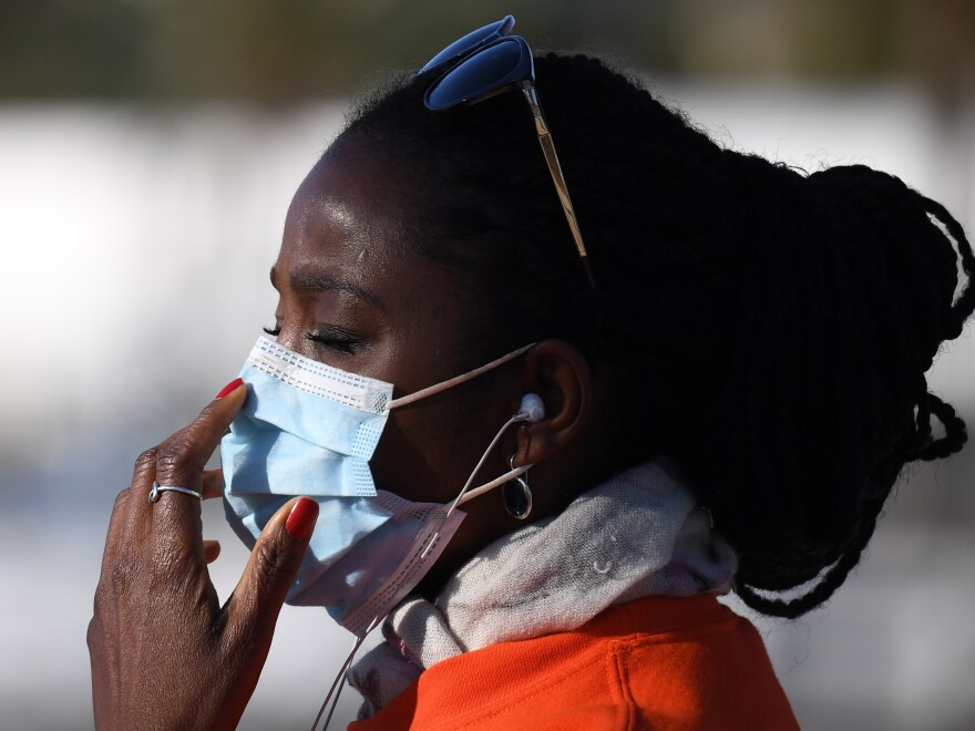 A woman adjusts her mask in Los Angeles, where the mayor already urged residents to wear face coverings in public.