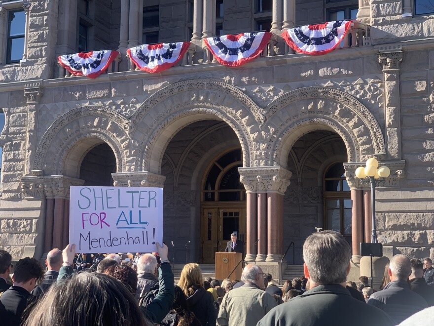 """Photo of a person holding a sign that reads """"Shelter for all Mendenhall!"""" at the inauguration of Erin Mendenhall as Salt Lake City mayor."""