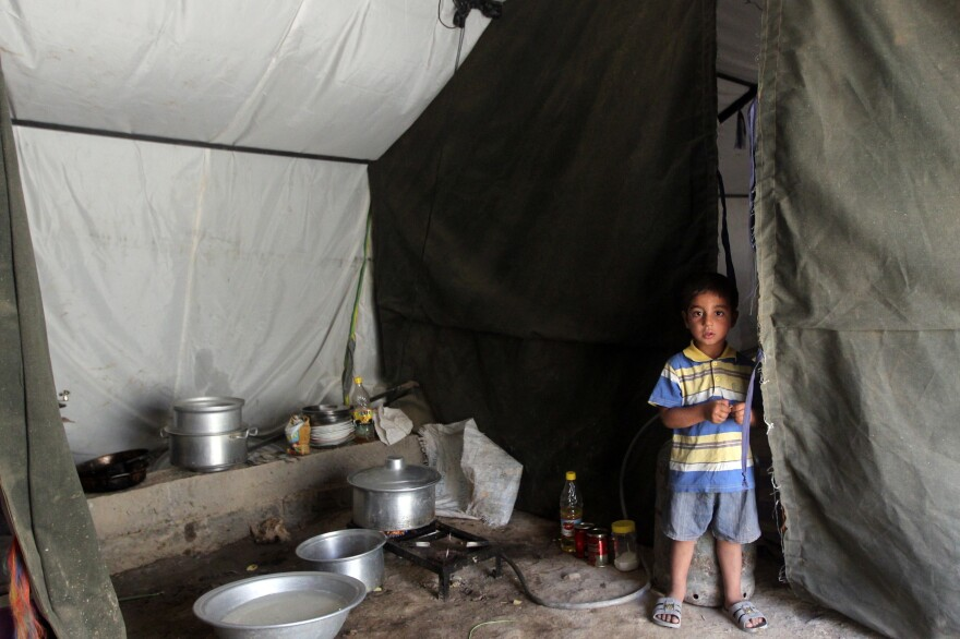 An Iraqi boy, whose family fled Ramadi after it was seized by the self-declared Islamic State, is now living in a tent camp for displaced families near the capital Baghdad. Many civilians fled the city and government forces are now attempting to regroup.