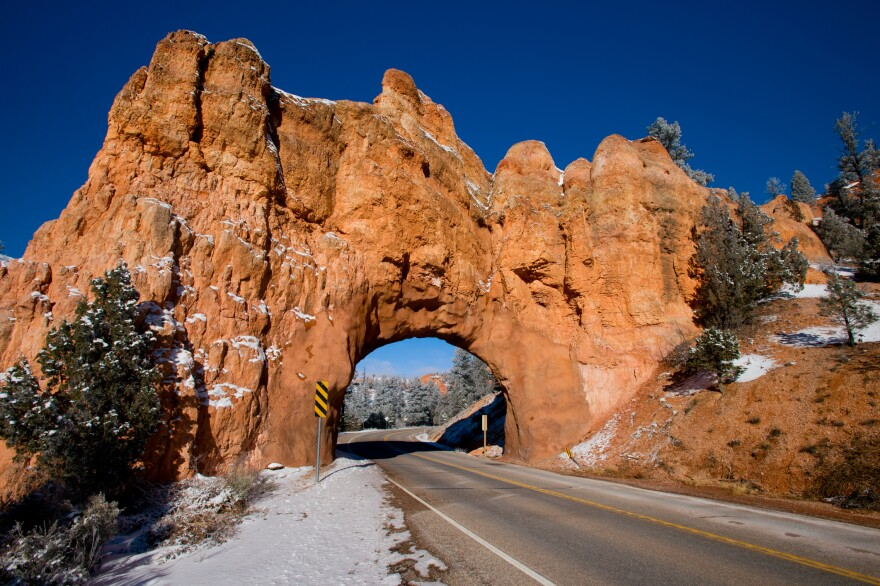 Snow brims the road on a blue sky day outside Bryce Canyon.