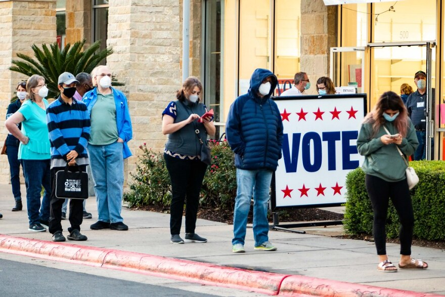 Voters wear masks in line at Southpark Meadows in South Austin on the first day of early voting in Texas.