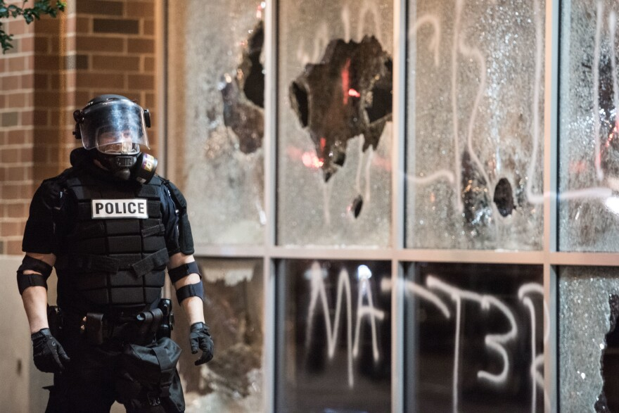A police officer in riot gear stands near a damaged storefront in uptown Charlotte, N.C., on Wednesday. The city's population of more than 800,000 people is about 45 percent white, 35 percent black and 13 percent Hispanic, according to the U.S. Census Bureau.