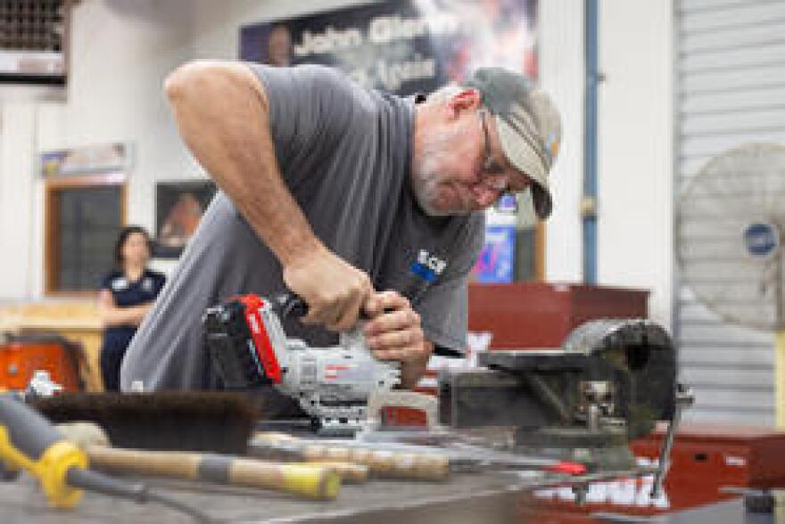SpaceWorks manager Dale Capps is working on metal brackets that he created in the fabrication shop. They will hold the monitor in place on a console. Original replacements are not available.