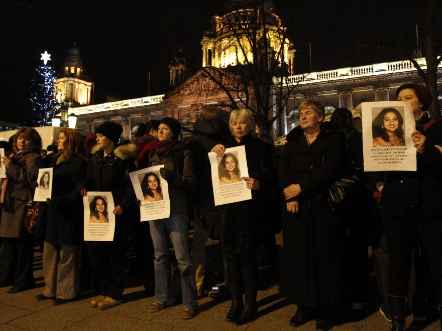 People hold pictures of Savita Halappanavar during a vigil outside Belfast City Hall, Northern Ireland, on Thursday. Halappanavar died Oct. 28 in Galway, Ireland, just days after she was denied an abortion.
