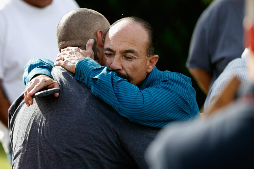 Jesus Gonzalez (left) and Pastor Ernie Ceballos (right) hug outside the crime scene where the suspects of the Inland Resource Center were killed on Wednesday in San Bernardino, Calif.