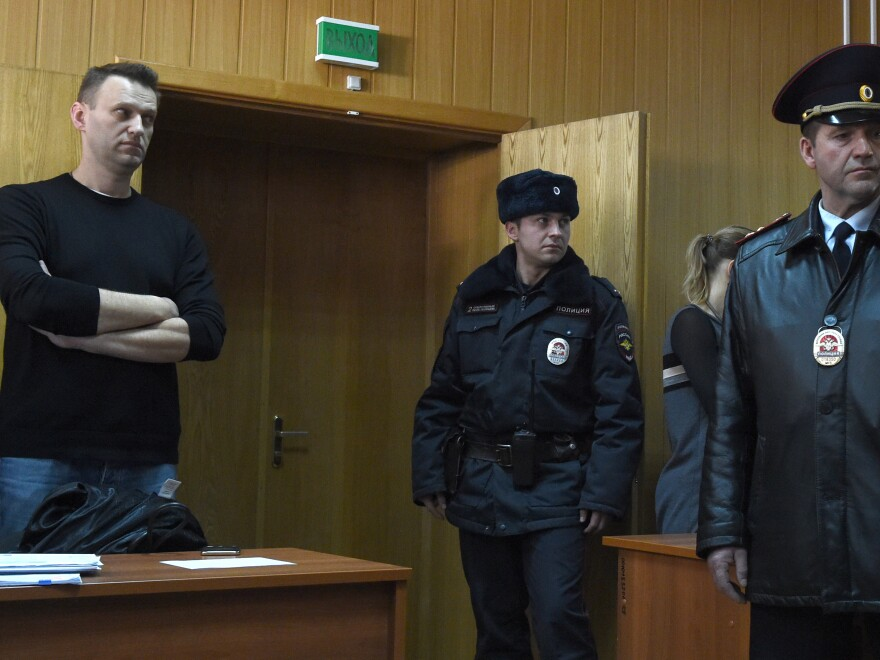 """Kremlin critic Alexei Navalny (left), who was arrested during a March 26 anti-corruption rally, attends a hearing at a court in Moscow on Monday. He was sentenced to 15 days behind bars and fined Monday after he and more than 1,000 other demonstrators were detained at an anti-corruption protest in Moscow that was branded a """"provocation"""" by the Kremlin."""