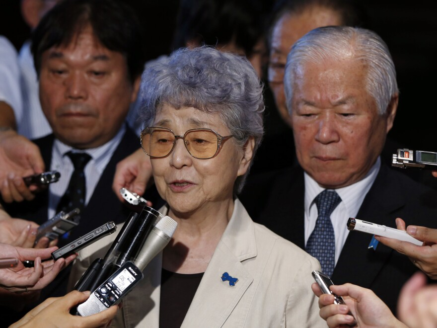 Shigeru Yokota, right, and his wife Sakie, center, whose daughter Megumi was abducted by North Korean agents in 1977, are surrounded by reporters following their meeting with Japan's Prime Minister Shinzo Abe on July 4, 2014. The family believes Megumi Yokota is alive, despite North Korea's claims that she died.