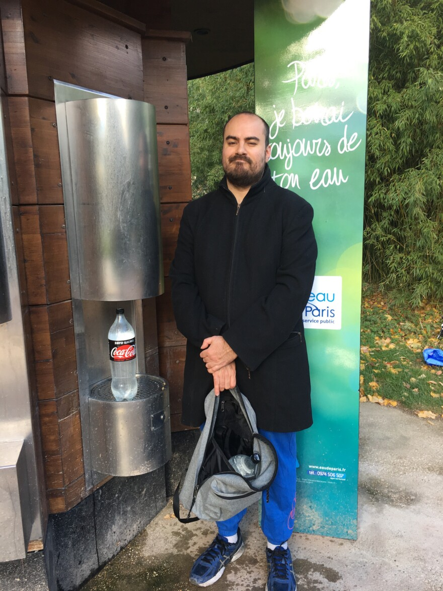 Artist Florian Roblain stops by Parc Andre Citroen in Paris to fill up a bottle with sparkling water at a public fountain.