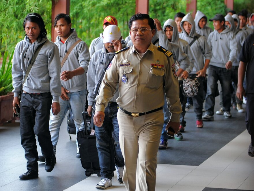 A Cambodian policeman escorts 30 fishermen returning home after being freed or escaping from slave-like conditions on Thai fishing vessels. The men arrived at the Phnom Penh airport in December. Large numbers of men from Myanmar and Cambodia are trafficked onto Thai fishing boats and forced to work in brutal conditions.