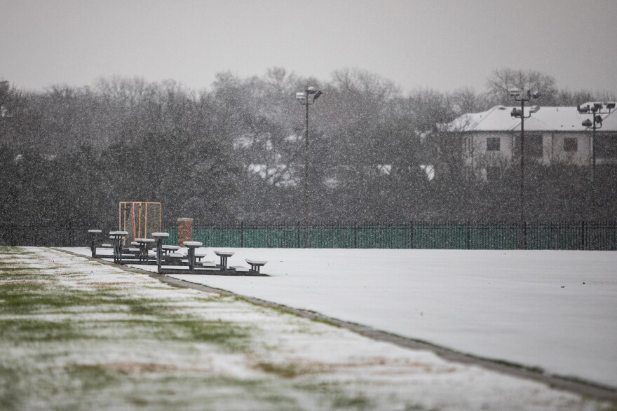 Snow falls at the UT intramural fields in Austin during a winter storm warning.