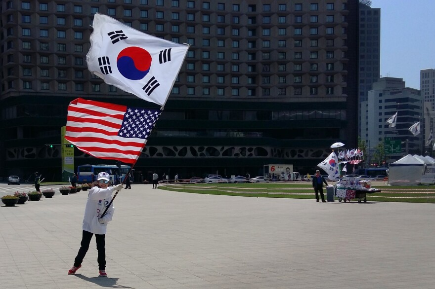 A demonstrator waves U.S. and South Korean flags together, at a pro-U.S. rally in front of Seoul's City Hall on Saturday.