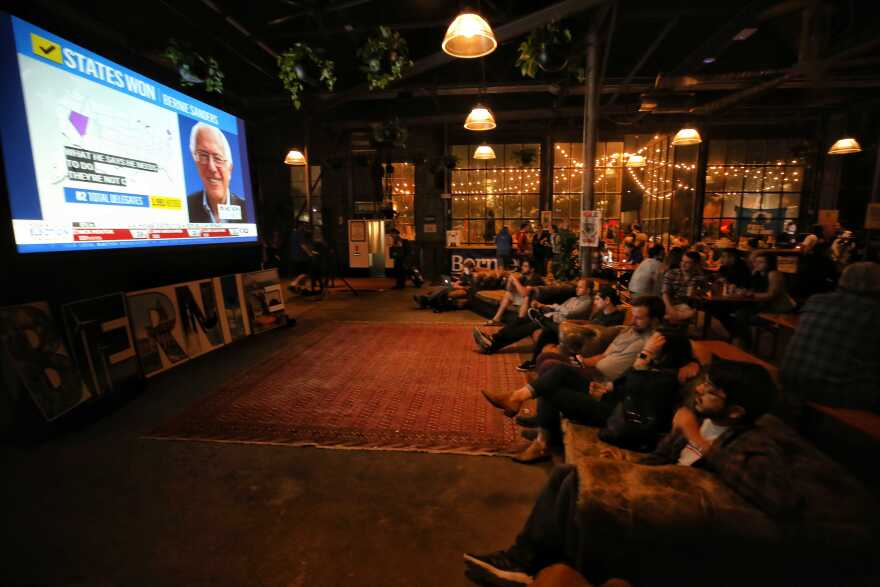 Bernie Sanders supporters watch election returns at a party at Central Machine Works on Tuesday.