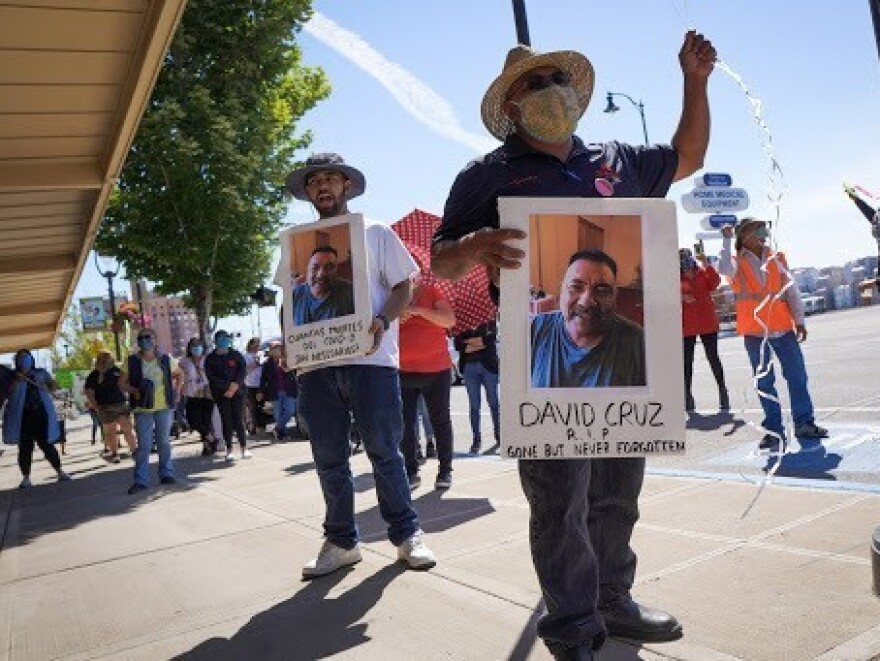 Farmworkers in Yakima, Washington's fruit packing industry walked off production lines in May and went on strike, demanding more protections against the coronavirus pandemic. Above, Emmanuel Anguiano-Mendoza (left) and Agustin López hold posters featuring David Cruz, a worker who died on May 30.