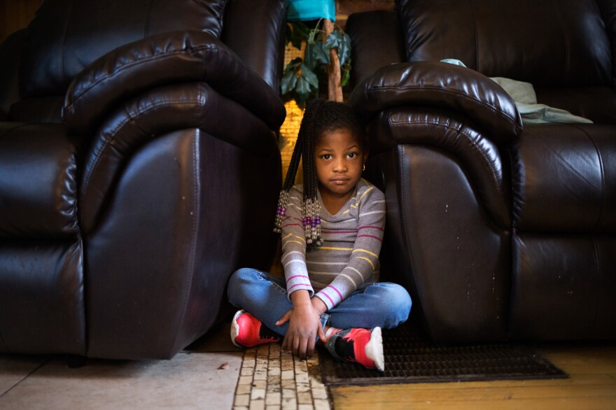 Five-year-old Amor Robinson shows where she went when she heard gunfire outside her grandmother's home in St. Louis. The narrow gap between the couch and armchair recliner became her hideaway.