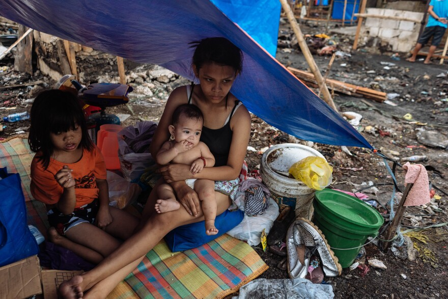 15-year-old Joy Villanueva (right) is seen with her baby after the slums where they lived burned down. She and her relatives hope to build a new shack to replace the home they lost.