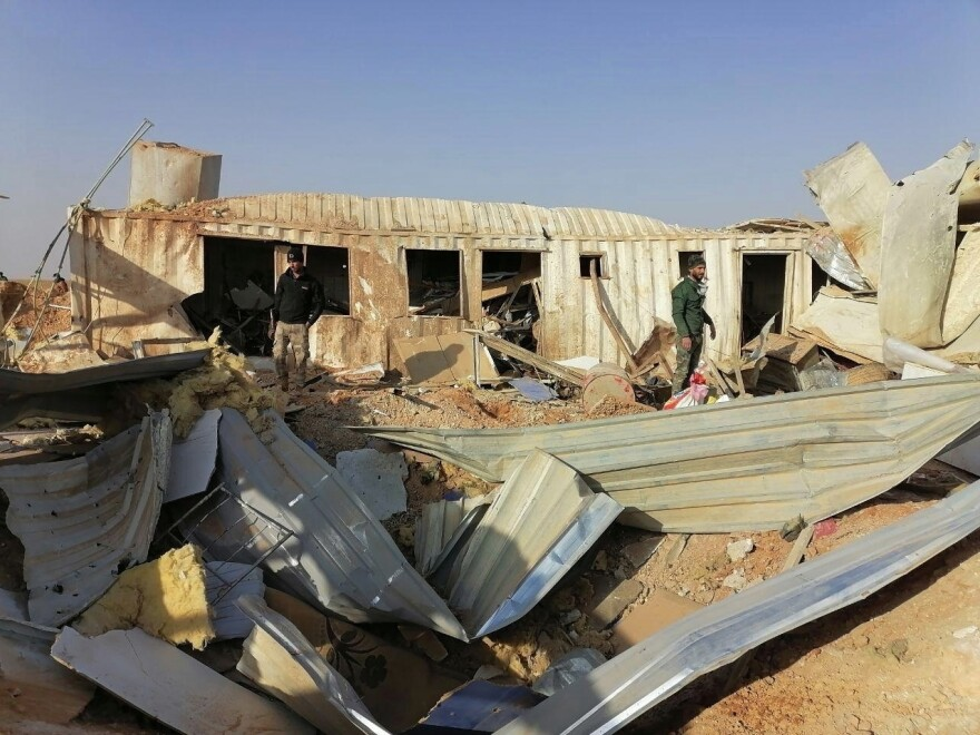 Fighters from the Kataeb Hezbollah militia inspect the destruction of their headquarters on Monday in the aftermath of a U.S. airstrike in Qaim, Iraq.