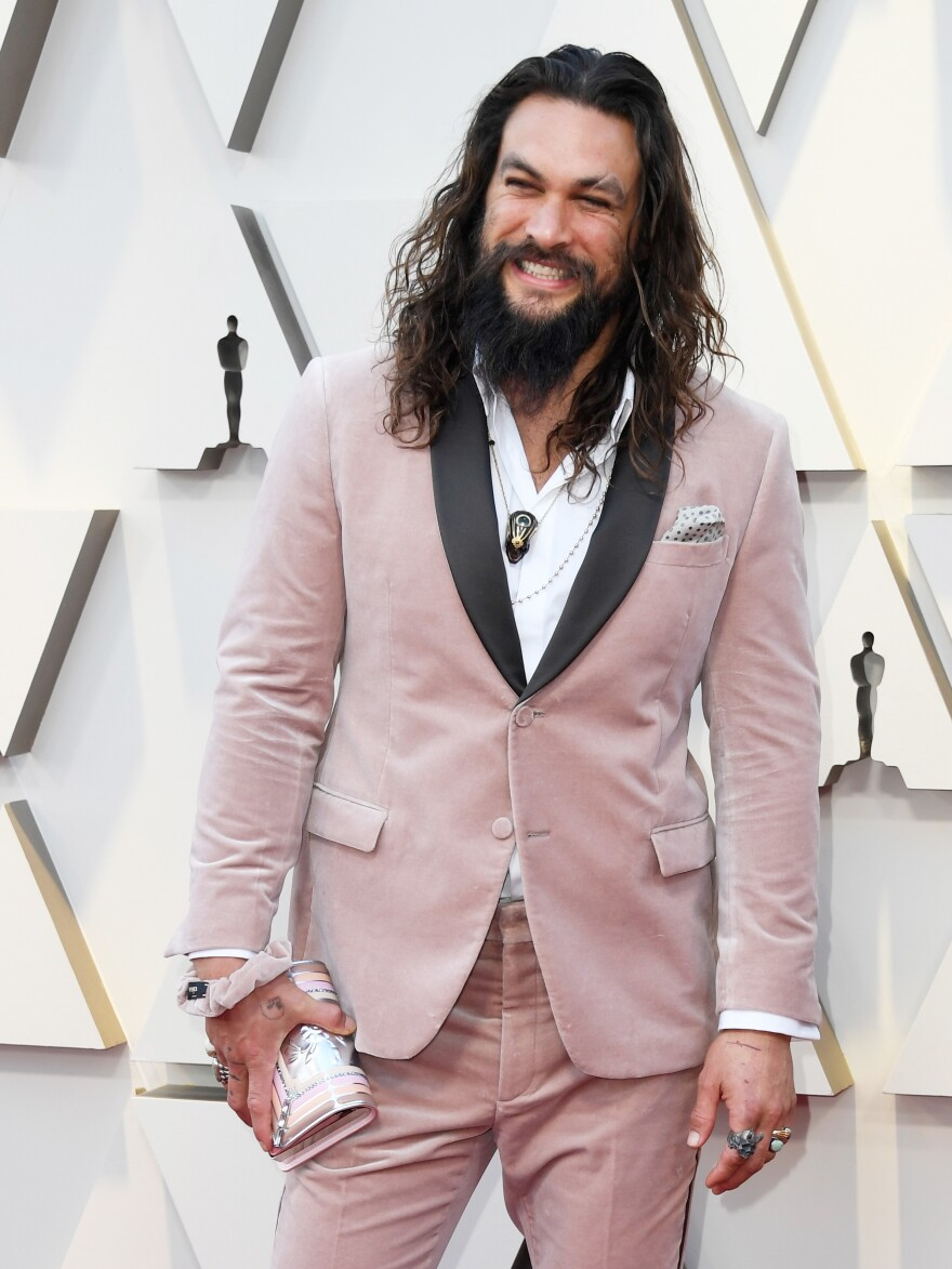 Actor Jason Mamoa wears a pink scrunchie on his wrist at the 2019 Academy Awards.