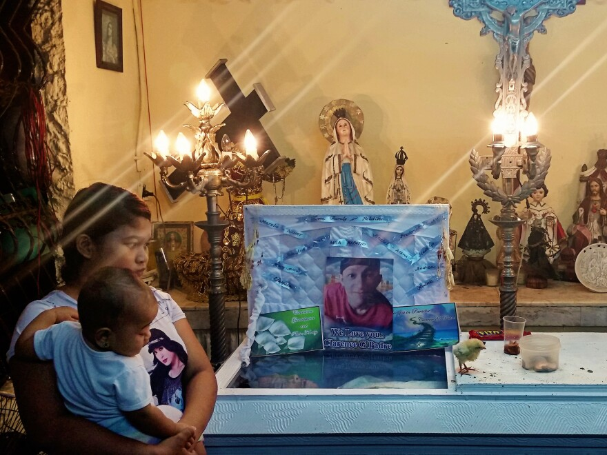 Clarence Jepadre's girlfriend Rachel Quebec stands with daughter Roseann in front of his casket. A chick paces on the coffin's lid. Jepadre, 17, was found stabbed to death. It's a tradition to place chicks on the coffins of murder victims to peck at the conscience of the killer.