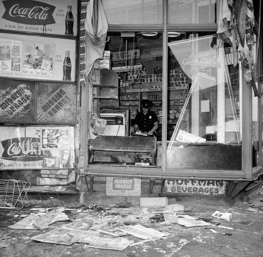 A policeman stands inside a grocery store with broken front windows in the Bedford-Stuyvesant section of Brooklyn on July 22, 1964.