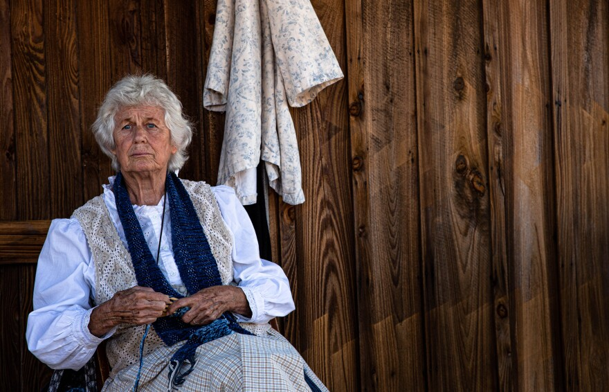 Joyce Cooper sits on a porch while practicing stick weaving.