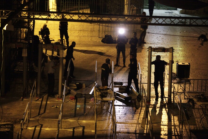 Workers dismantle metal detectors early Tuesday outside Al-Aqsa Mosque compound in Jerusalem's Old City.