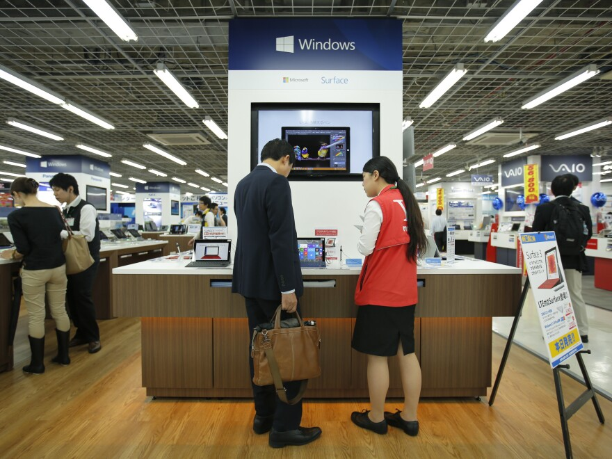 A sales clerk speaks with a customer in front of Microsoft Corp.'s display at an electronics store in Tokyo. Microsoft's division in Japan says it saw productivity grow by 40% after allowing employees to work for four days a week rather than five.