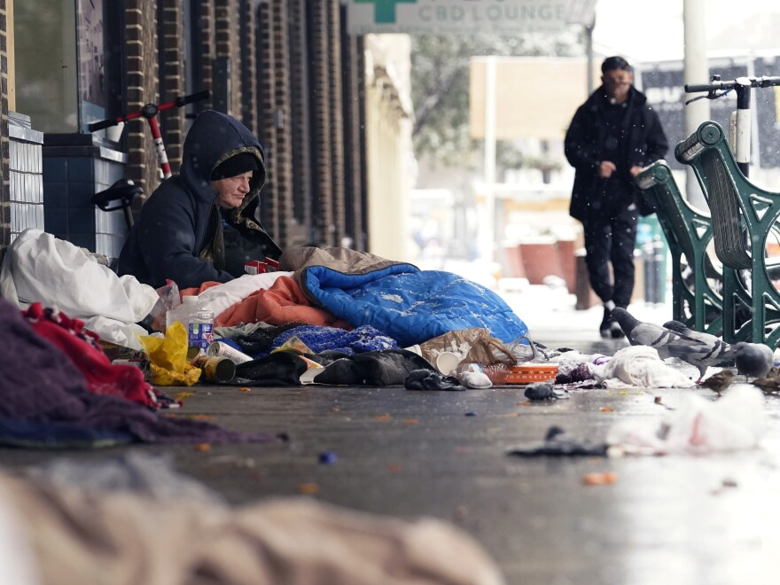 A woman living on the streets uses blankets to keep warm, Thursday in downtown San Antonio. Snow, ice and subfreezing weather continue to wreak havoc on the state's power grid and utilities.