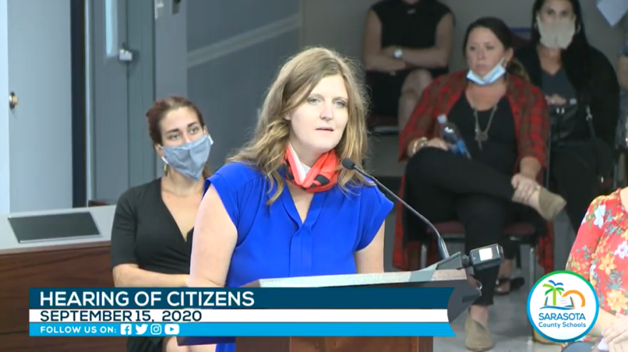 Woman in blue shirt with Trump gaiter draped around neck speaks during public comment