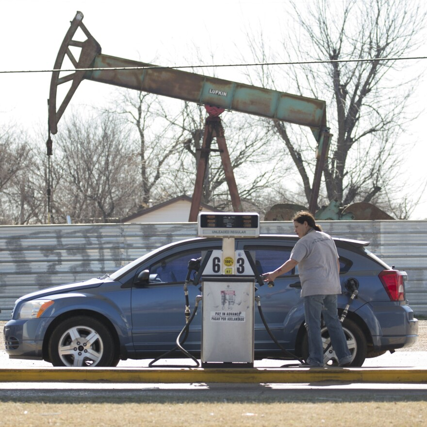 A motorist fills her car at a gas station near an oil field pumping rig in Oklahoma City.