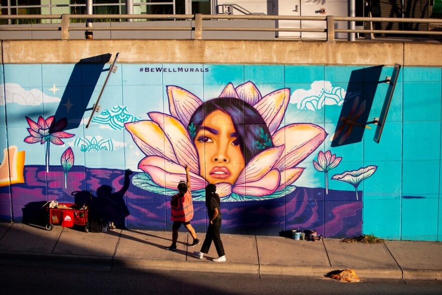 Carmen Rangel paints a mural of a woman coming out of a flower on the North Lamar underpass
