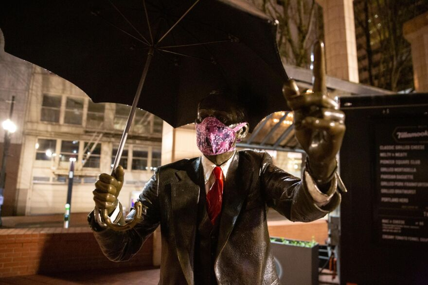 The Umbrella Man statue wears a mask in Pioneer Courthouse Square in Portland, Ore., Saturday, April 18, 2020. Public health officials have encouraged people to wear masks to slow the spread of COVID-19.