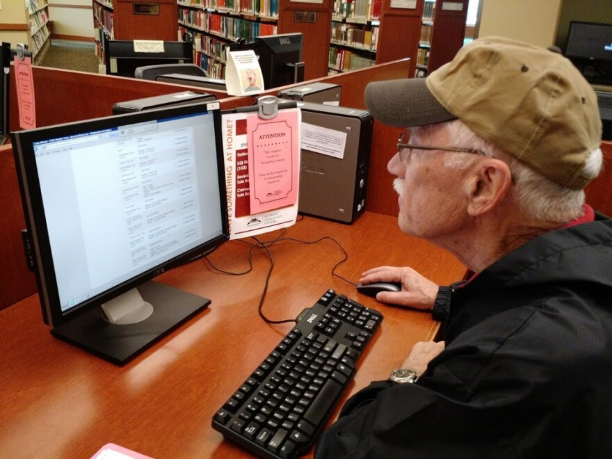 Man researching family genealogy on a computer in a library.