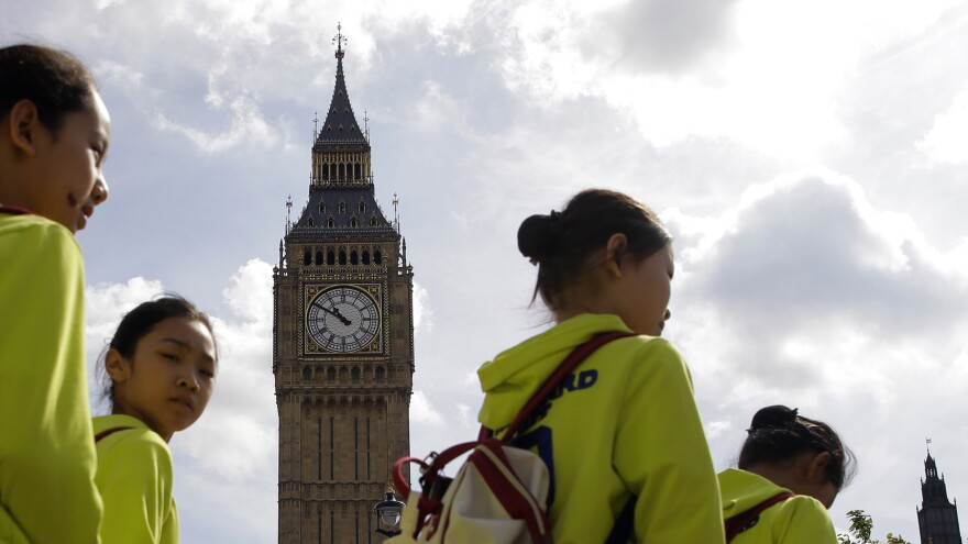 Tourists walk past the Palace of Westminster and Big Ben in London. Big Ben is scheduled to fall silent next week.