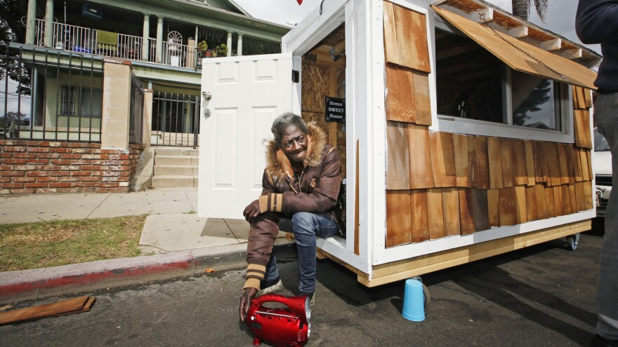 """Irene """"Smokie"""" McGhee, a woman who had been sleeping on the streets in a South Los Angeles neighborhood, listens to music in the doorway of her newly built tiny home last May."""