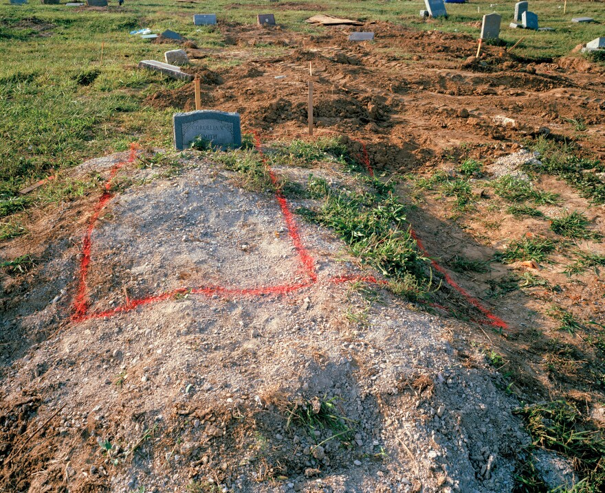 Graves outlined in rectangular red spraypaint during relocation efforts.