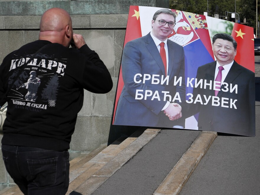 "A man protests the declaration of a state of emergency last week in Belgrade with a banner showing Serbian President Aleksandar Vucic, left, and China's President Xi Jinping. The banner reads, ""Serbs and Chinese Brothers Forever."""