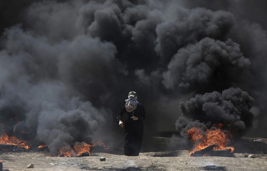 A Palestinian woman walks through black smoke from burning tires during a protest on the Gaza Strip's border with Israel.