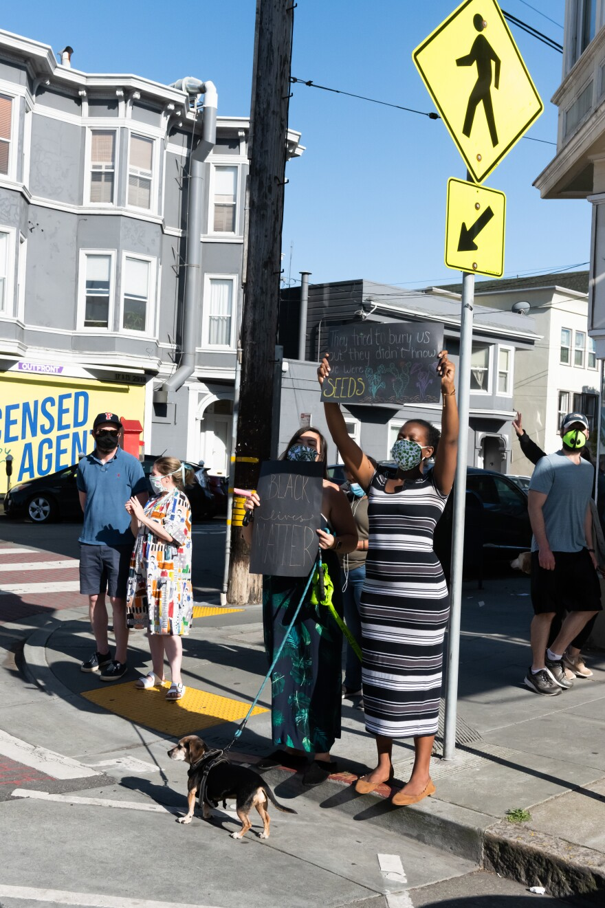 A protester holds a sign up in San Francisco as a caravan of cars drives by, in a socially distanced demonstration denouncing police brutality against black Americans. Bikers, pedestrians and residents along the caravan route participated in the protest.