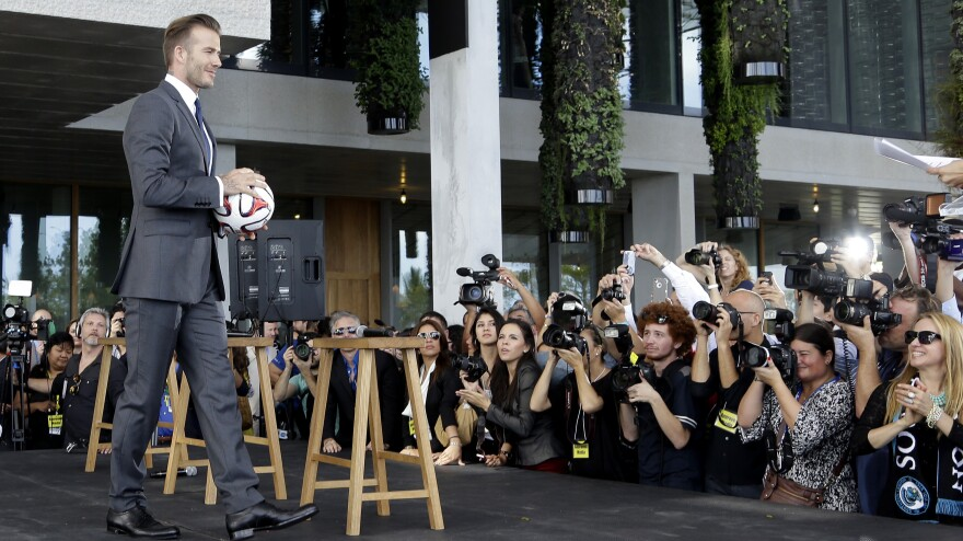 Former soccer star David Beckham holds a ball at a news conference where he announced he's exercising an option to buy a Major League Soccer expansion team in Miami.